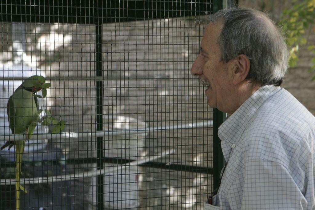 Romano Dezi  con uno dei pappagalli delle voliere esterne