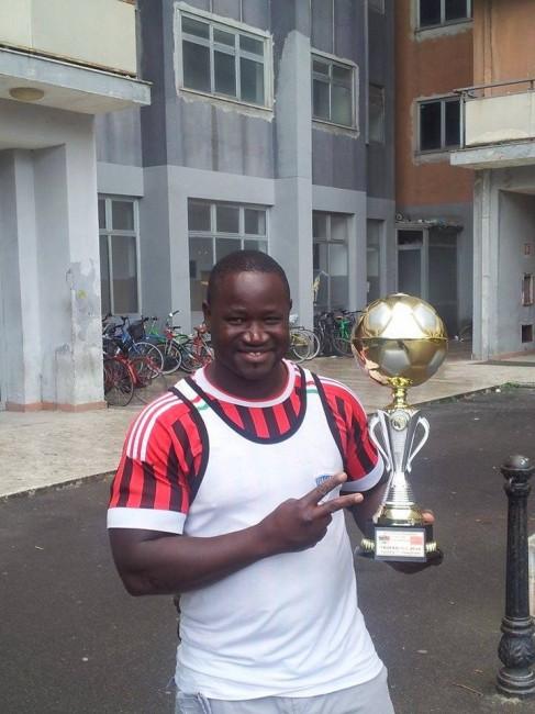 Moussa Ngom, 42 anni, lavora in fabbrica e allena la squadra dell'associazione Guy Ghi. Qui mostra fiero una coppa vinta in un recente torneo