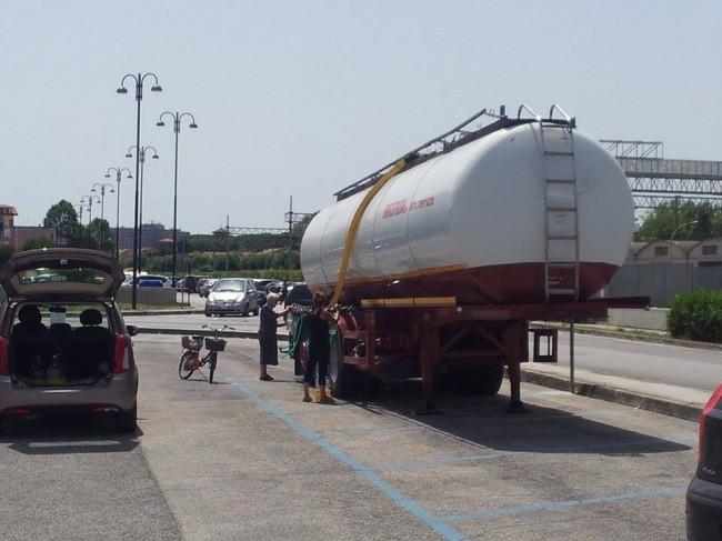 Alcuni cittadini si riforniscono stamani all'autobotte di via Galilei