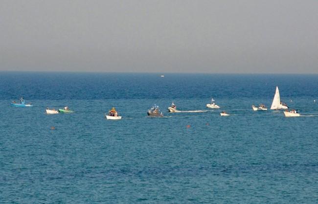 Limbarcazione-con-a-bordo-il-sindaco-Montali-è-attorniata-da-gommoni-natanti-e-motoscafi.-Cè-anche-una-barca-a-vela.