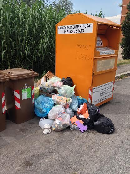 I sacchetti abbandonati vicino alla raccolta di vestiti usati in via Cassiano da Fabriano
