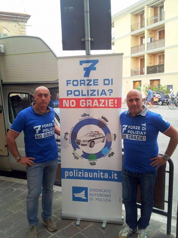 Gianluca Romagnoli, segretario provinciale Sap, e Roberto Feliziani, della Stradale di Porto Recanati, posano accanto allo slogan per l'unificazione delle forze di polizia.