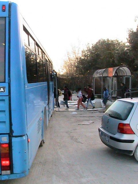 I bambini che prendono lo scuolabus all'Hotel House, passando lungo una passerella di legno posta sopra il terreno fangoso
