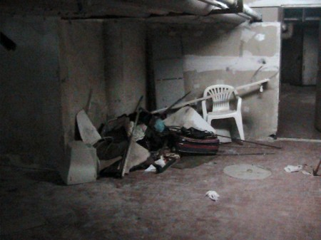Sedie e rifiuti nel corridoio tra i garage sotterranei.