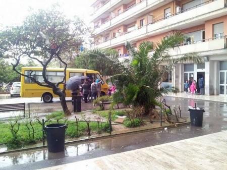 Hotel House --- L'arrivo di un pulmino nel piazzale invaso dalla pioggia. Le spese condominiali all'Hotel House ammontano a 80 euro mensili