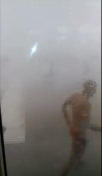 Un bagnante si mette al riparo dalla tromba d'aria allo stabilimento Federico