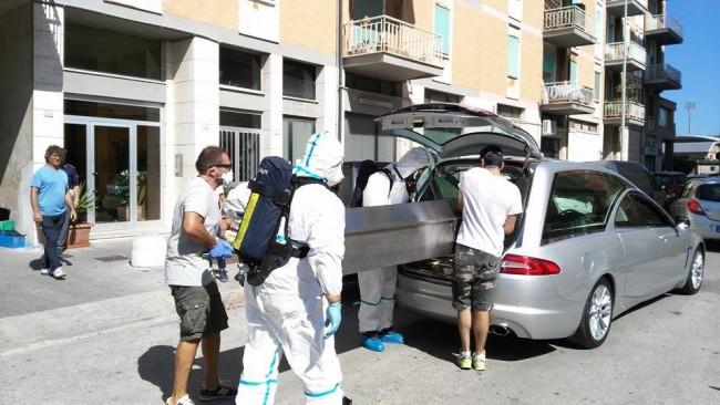 Il cadavere rinvenuto nel garage mentre viene caricato sul carro funebre