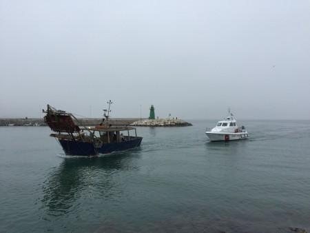 Una delle vongolare uscite in mare mentre rientra in porto scortata dalla Capinateria