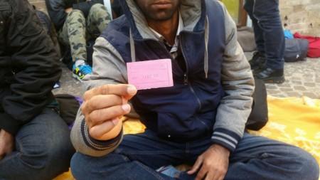 Uno dei profughi mostra un bigliettino con la data dell'11 dicembre, quando gli hanno preso le impronte digitali
